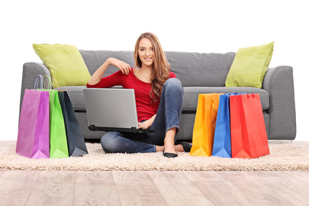 clothes shopping: Young woman holding a laptop seated in front of a modern gray sofa with a bunch of shopping bags on the floor around her isolated on white background Stock Photo