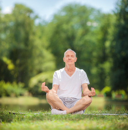 relief: Peaceful senior man meditating seated on a blanket in a park by a lake shot with tilt and shift lens
