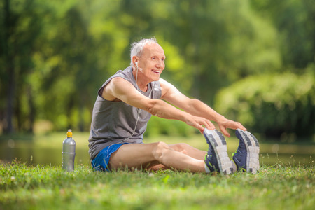 stretches: Joyful senior stretching his legs in a park and listening to music on headphones seated on the grass by a pond