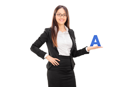 beautiful teacher: Young female school teacher in a black suit holding the letter A and looking at the camera isolated on white background