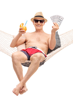 Vertical shot of a joyful senior man in a swim trunks drinking a cocktail and holing a stack of money seated in a hammock isolated on white background Stock Photo