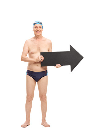 one way: Full length portrait of a senior man in a black swim trunks holding a big black arrow pointing right and looking at the camera isolated on white background