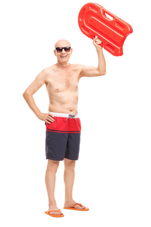 swimming to float: Full length portrait of a shirtless senior holding a swimming float up in the air and looking at the camera isolated on white background