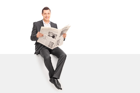 newspaper: Young businessman holding a newspaper seated on a blank signboard and looking at the camera isolated on white background Stock Photo