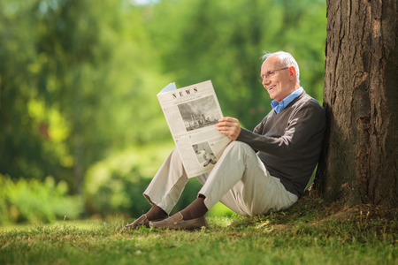 Cheerful senior gentleman reading a newspaper in park and leaning against a tree seated on the ground on beautiful summer day Banque d'images