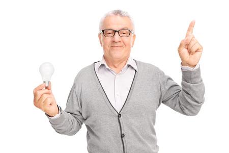 ancianos felices: Caballero mayor que sostiene una bombilla y apuntando hacia arriba con el dedo aislado en el fondo blanco
