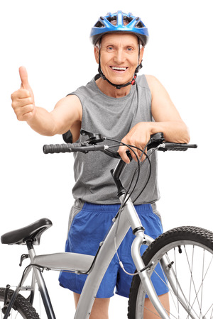 Vertical studio shot of a senior with a blue helmet posing behind a bicycle and giving a thumb up isolated on white background