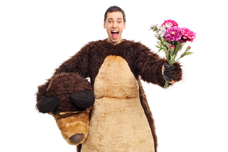 overjoyed: An overjoyed guy in a bear costume handing a bouquet of flower towards the camera isolated on white background