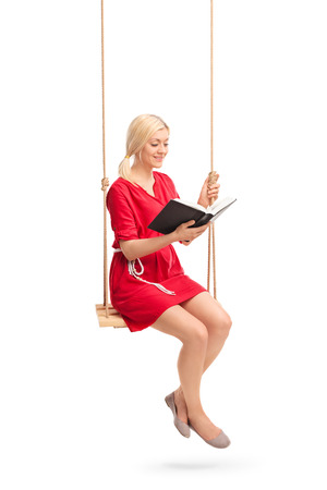 girl woman: Vertical shot of a young woman in a red dress sitting on a swing and reading a book isolated on white background Stock Photo
