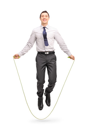 skipping rope: Full length portrait of a young cheerful businessman jumping a rope and looking at the camera isolated on white background Stock Photo