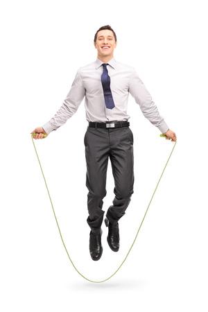 saltar la cuerda: Retrato de cuerpo entero de un hombre de negocios alegre joven saltando una cuerda y mirando a la c�mara aislada en el fondo blanco