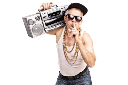 rap music: Mature man in hip-hop clothes carrying a ghetto blaster over his shoulder and holding a finger on his lips isolated on white background