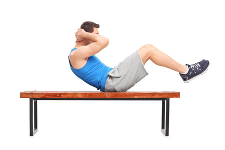 doing: Young male athlete doing stomach crunches on a wooden bench isolated on white background Stock Photo