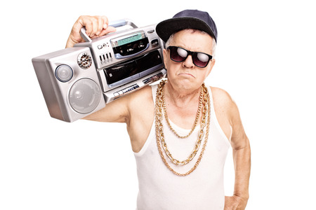 blaster: Serious senior rapper holding a ghetto blaster over his shoulder and looking at the camera isolated on white background