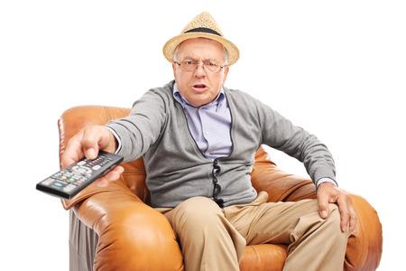 enojo: Hombre mayor enojado pulsando botones en un mando a distancia sentado en un sillón aislado en fondo blanco Foto de archivo