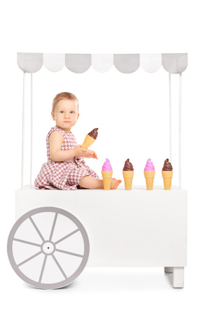 ice cream stand: Cute little baby girl holding an ice cream cone seated on an ice cream stand isolated on white background