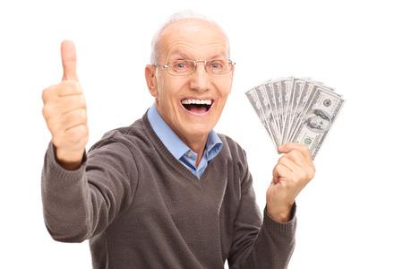 vzrušený: Nadšený senior gentleman drží hromadu peněz a dává palec nahoru na bílém pozadí
