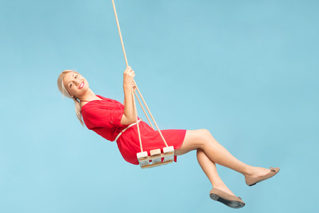 swing seat: Carefree blond woman swinging on a wooden swing and looking at the camera on blue background Stock Photo