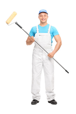 painter and decorator: Full length portrait of a young male house painter in a white overalls holding a paint roller and looking at the camera isolated on white background Stock Photo