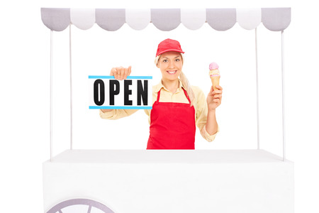 ice cream stand: Young female vendor holding an ice cream cone and an open sign behind an ice cream stand isolated on white background Stock Photo