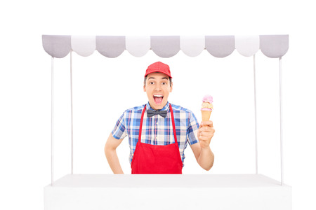 ice cream stand: Excited young vendor with a red cap and apron holding an ice cream cone behind an ice cream stand isolated on white background