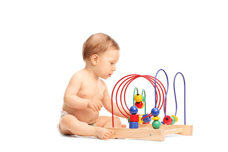 seated: Cute little baby playing with a toy seated on the floor isolated on white background