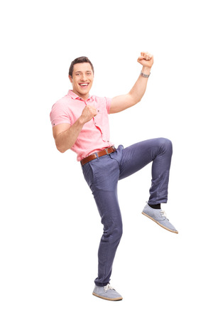 Full length portrait of an excited young guy gesturing happiness and looking at the camera isolated on white background Stock Photo
