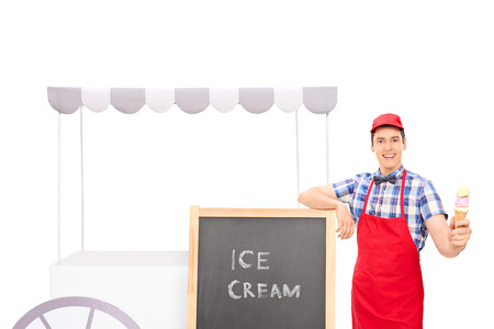 ice cream stand: Young male vendor standing by an ice cream stand and holding an ice cream cone isolated on white background