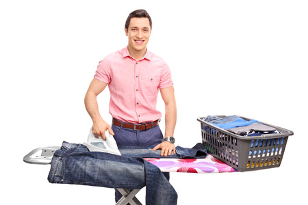 man laundry: Cheerful young man ironing a pair of jeans on an ironing board and looking at the camera isolated on white background