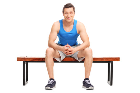 attitudes: Young sportsman sitting on a wooden bench and looking at the camera isolated on white background