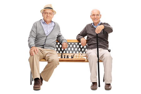 Two old men posing seated on a wooden bench with a chessboard between them isolated on white background