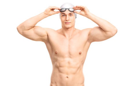 swimmers: Muscular young swimmer with a gray swim cap and black swimming goggles looking at the camera and smiling isolated on white background