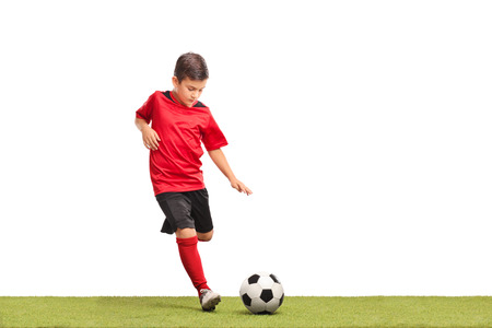 white background: Little kid in red football jersey kicking a football on a grass surface isolated on white background