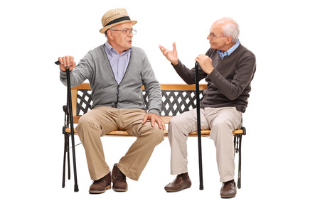 senior friends: Studio shot of a two senior gentlemen having a conversation seated on a wooden bench isolated on white background Stock Photo