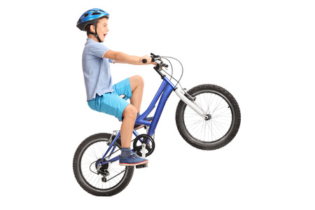 Profile shot of a little boy with blue helmet doing a wheelie on a small blue bike isolated on white background
