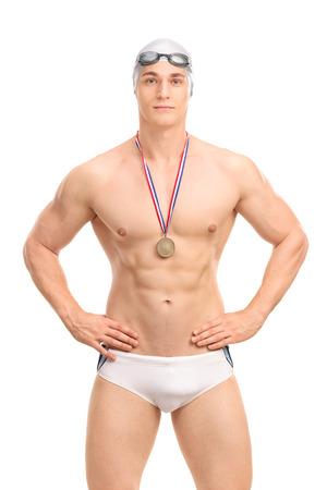 ganador: Tiro vertical de un apuesto joven campe�n de nataci�n en traje de ba�o de color blanco sobre fondo blanco Foto de archivo