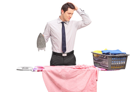 Studio shot of a confused young guy trying to iron his clothes isolated on white background Stock Photo