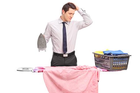 confundido: Tiro del estudio de un individuo joven confuso que intenta planchar la ropa aislada en el fondo blanco