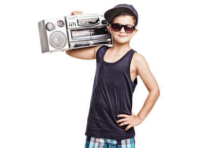 rap music: Cool boy in hip hop outfit holding a ghetto blaster over his shoulder and looking at the camera isolated on white background