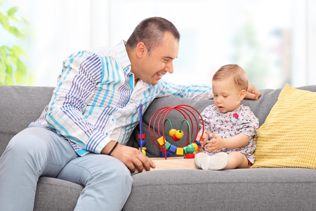 family playing: Young father playing with his baby daughter seated on a gray sofa at home Stock Photo