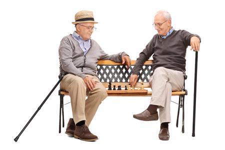 jugando ajedrez: Estudio tirado de dos ancianos jugando una partida de ajedrez sentado en un banco de madera aislada sobre fondo blanco Foto de archivo