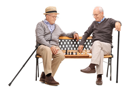 playing chess: Studio shot of two seniors playing a game of chess seated on a wooden bench isolated on white background