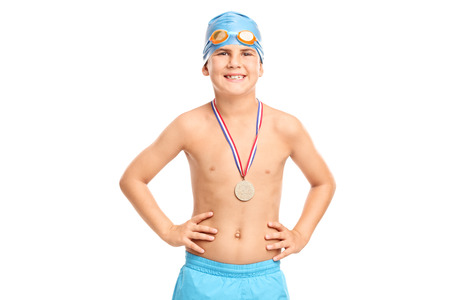trunks: Junior swimming champion with blue swim cap and swim trunks looking at the camera isolated on white background Stock Photo
