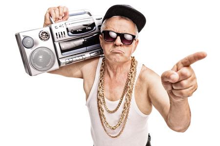 Grumpy senior Rapper, der einen Ghettoblaster auf die Schulter und zeigt mit dem Finger auf weißem Hintergrund