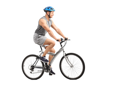 Full length profile shot of a young male biker riding a bicycle isolated on white background