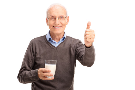 posing  agree: Senior gentleman holding a glass of milk and giving a thumb up isolated on white background