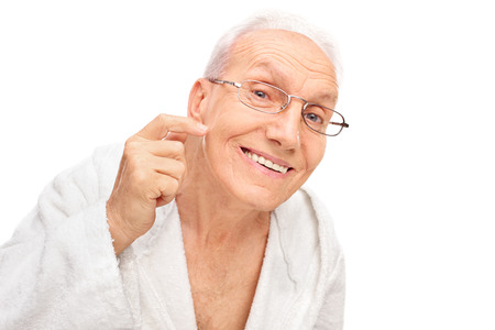 aging skin: Studio shot of a joyful senior checking his skin and looking at the camera isolated on white background Stock Photo