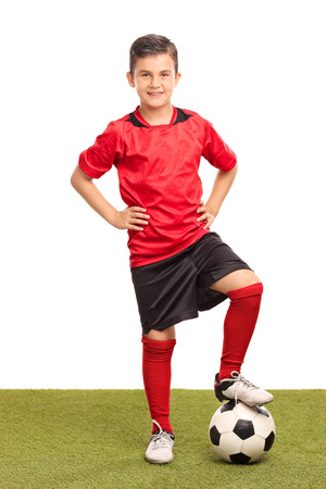 junior soccer: Full length portrait of a junior soccer player stepping over a soccer ball and looking at the camera isolated on white background Stock Photo