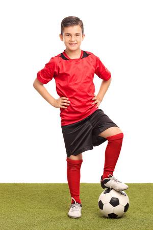 jugadores de futbol: Retrato de cuerpo entero de un jugador de fútbol infantil pasando por encima de una pelota de fútbol y mirando a la cámara aislada en el fondo blanco