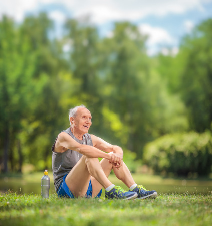 Athletic senior in sportswear sitting on grass in a park and listening to music on headphones shot with tilt and shift lens